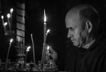 Kiev - geestelijke brandt een kaars